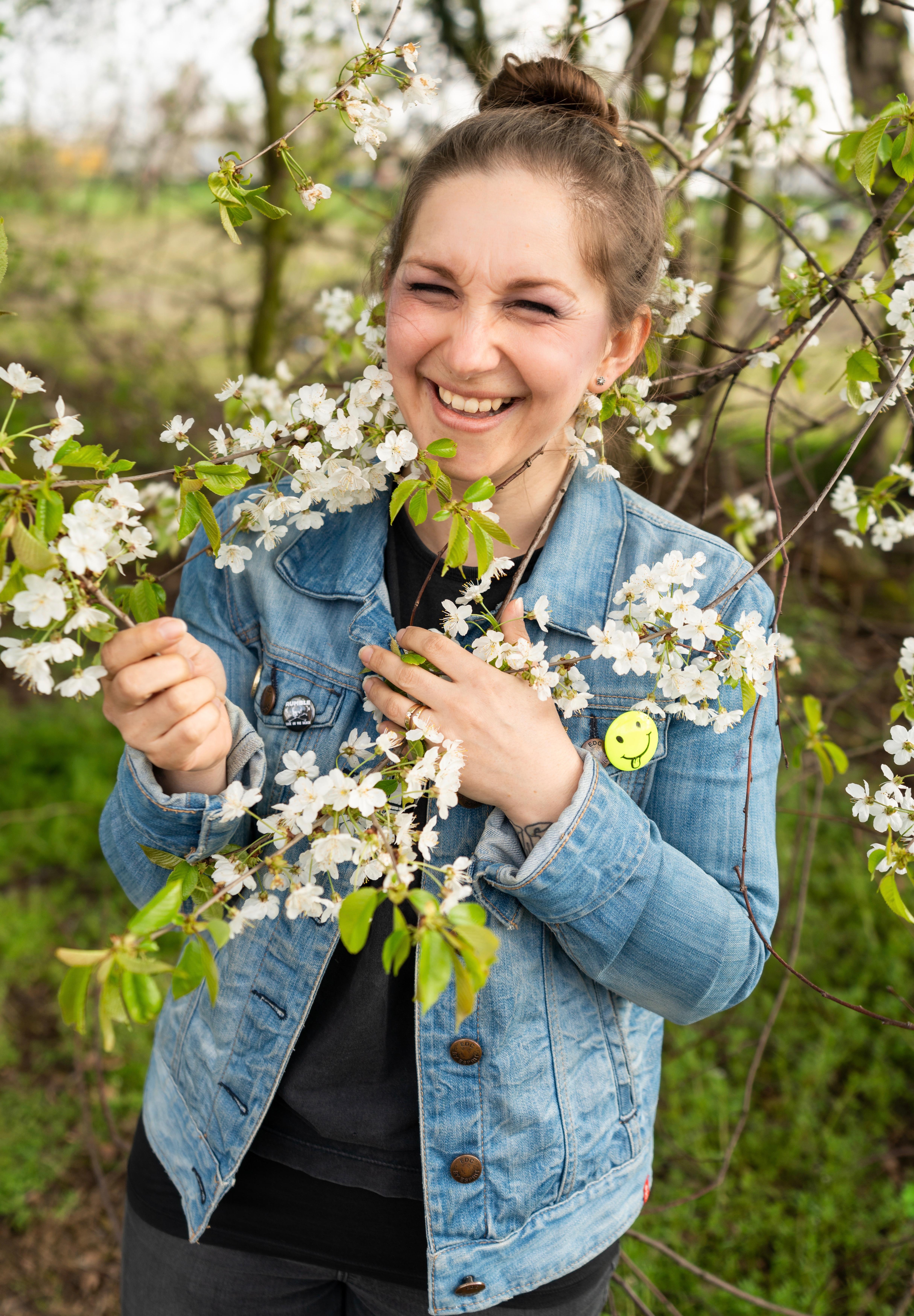 junge, lachende Frau mit Dutt und Jeansjacke hält Ast mit weissen Blüten in den Händen